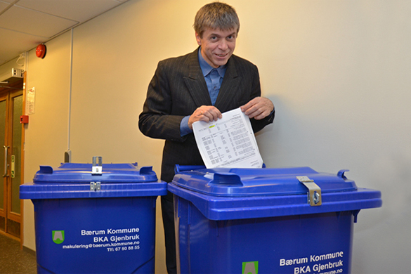 Bildet viser kommneadvokaten som legger dokumenter i en blå returkontainer fra Sikkerhetsavdelingen på Rud.