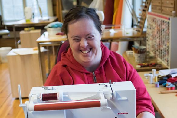 Portrettbilde av arbeidstaker Ann-Kristin, som sitter ved symaskinen på tekstilavdelingen.
